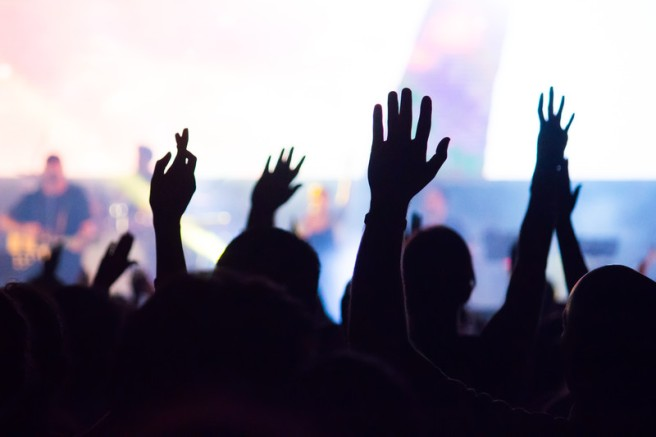 people raising hands in a church service